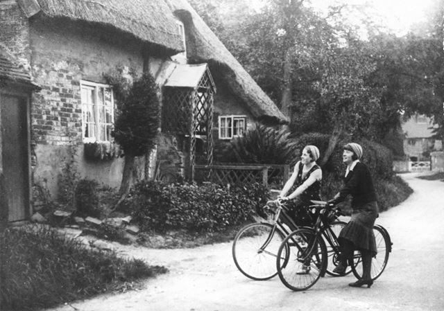 Two lady cyclists looking at the cottages at Hemington Hill