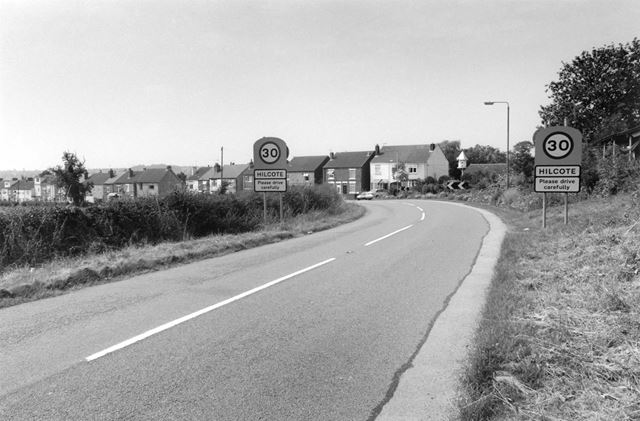 View up New Lane, Hilcote, showing village signs