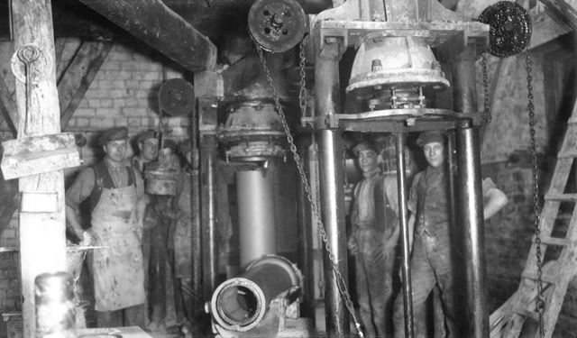 Pipe making machines and workmen at the brick and sanitary pipe works of W H and J Slater, Denby