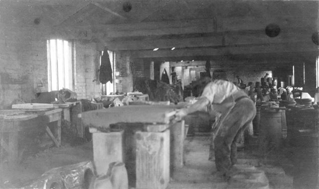 Interior of the workshops, cutting a 'batt' of clay at the brick and sanitary pipe works of W H and