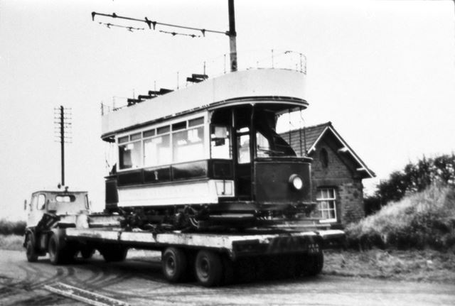 Open topped tram being transported by lorry