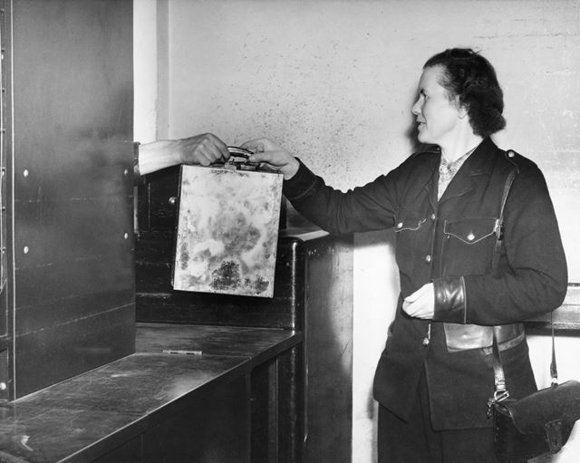 Derby Corporation bus conductress handing in a cash box