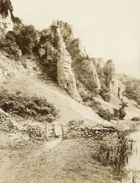 Woman at gate. Entrance to Dovedale