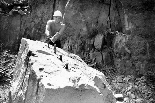 Quarryman splitting stone with 'plugs and feathers'