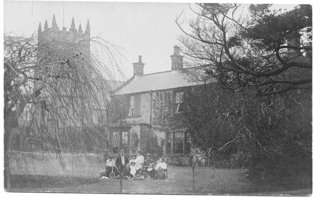 Group of people in garden with Morton Church behind