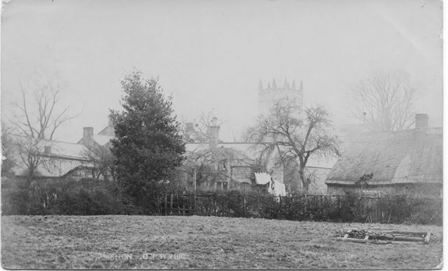 View of houses and church across fields